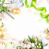 Festive Happy Easter background with decorated eggs, flowers, candy and ribbons in pastel colors on white. Copy space. Festive Easter background with decorated royalty free stock image