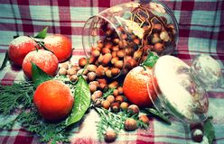 Nuts in a glass vase with tangerines stock photos