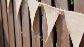 Festive garland of triangle linen flags on wooden fence at summer day on holiday stock footage