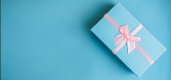 Festive holiday New Year and Christmas blue background with gift box. Concept of carnival, birthday, party. Flat lay stock photos