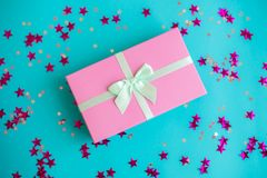Festive holiday New Year and Christmas blue background with gift box, confetti, stars. Concept of carnival, birthday stock image