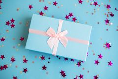 Festive holiday New Year and Christmas blue background with gift box, confetti, stars. Concept of carnival, birthday stock images