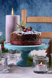 Festive holiday table with English style Christmas fruit cake. With glamorous table setting with pink candles and blue background., closeup Royalty Free Stock Photo