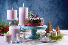 Festive holiday table with English style Christmas fruit cake. With glamorous table setting with pink candles and blue background, with copy space Stock Images