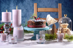 Festive holiday table with English style Christmas fruit cake. With glamorous table setting with pink candles and blue background Royalty Free Stock Images