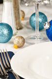 Festive Holiday Table Setting. Christmas ornaments in blues and gold decorate a festive holiday table with an empty white plate providing copy space Stock Photo