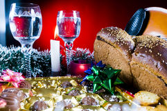 Festive holiday table setting. With glass goblets, a loaf of bread, chocolate candy, snacks, violin, bows and garland Stock Photos