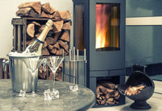 Festive home interior wirh champagne, two glasses and fireplace Royalty Free Stock Images