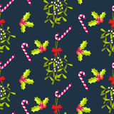 Festive kissing bough seamless vector pattern. Traditional plant tied with red bow. Holly berry and stripes candy cane blue background Stock Images