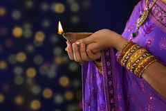 Festive of light. Diwali or festive of lights. Traditional Indian festival, woman in sari hands holding oil lamp, with defocus light background Royalty Free Stock Image