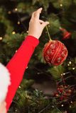 Festive little girl hanging a christmas decoration Stock Images