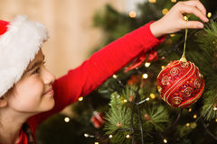 Festive little girl hanging a christmas decoration Royalty Free Stock Images