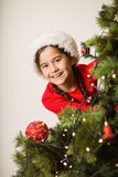 Festive little girl hanging a christmas decoration Royalty Free Stock Image
