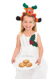 Festive little girl holding fresh cookies Royalty Free Stock Image