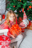 Festive little girl opening a gift at home Stock Photography
