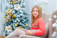 Festive little girl opening a gift at home Stock Photo
