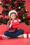 Festive little girl opening a gift Stock Photo