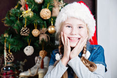 Festive little girl smiling camera against home with christmas tree Stock Photo