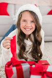 Festive little girl smiling at camera with gifts Royalty Free Stock Photos