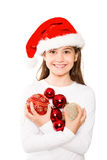 Festive little girl smiling at camera holding baubles Stock Photo