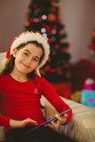 Festive little girl using tablet pc on couch Stock Images
