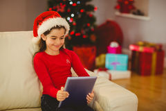 Festive little girl using tablet pc on couch Royalty Free Stock Photos