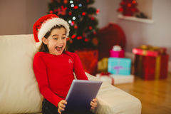 Festive little girl using tablet pc on couch Stock Image