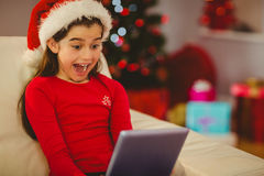 Festive little girl using tablet pc on couch Royalty Free Stock Photo