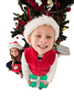 Festive little siblings smiling at camera holding gifts Stock Images