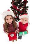 Festive little siblings smiling at camera holding gifts Royalty Free Stock Photo