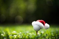 Festive-looking golf ball on tee with Santa Claus` hat