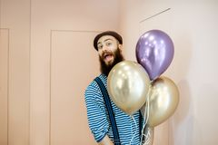 Festive man with balloons indoors