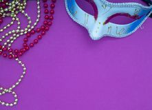 Festive mardi gras venetian carnivale. Festive mardi gras venetian or carnivale mask on a purple background, Empty space for design royalty free stock images