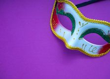 Festive mardi gras venetian carnivale. Festive mardi gras venetian or carnivale mask on a purple background, Empty space for design royalty free stock photos