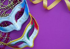 Festive mardi gras venetian carnivale. Festive mardi gras venetian or carnivale mask on a purple background, Empty space for design royalty free stock photography