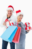 Festive mature couple in winter clothes holding gifts and bags Royalty Free Stock Image
