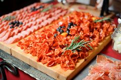 Festive meat appetizer consisting of delicious salami plate. Festive set of meat appetizer consisting of delicious salami plate decorated with black olives and Stock Image