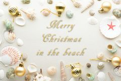 Festive Merry Christmas greeting text surroundedby a frame of baubles and seashells for a summer or tropical theme. Festive Merry Christmas greeting text Stock Image