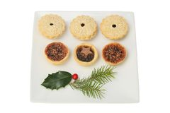 Festive mince pies. On a plate with holly and pine needles isolated against white stock image