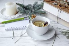 A festive mock up photo with a fir twigs, an opened note book, an old book, a pencil, cones, a candle and decation elements. A festive winter mock up photo with Stock Images