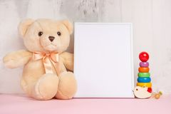 Festive mood, baby toys with white empty frame for layout design. Baby shower