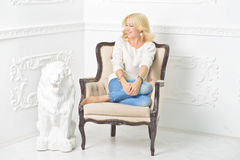 A festive mood. Happy young girl sitting in a beige armchair,dressed in a white jacket and denim pants.Plaster sculpture of a lion is behind the chair Stock Photography
