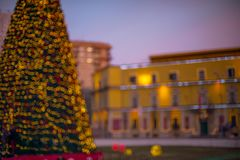Festive mood in Tirana center. Defocused image of New Year decorative lights of Christmas tree in Tirana center and illuminated ministerial buildings in the Royalty Free Stock Images