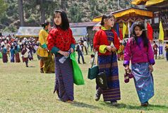 Festive Moods. Adolescent girls traditional dress during the Paro Tsechu (religious festival) in The Kingdom of Bhutan in the land of the thunder dragon high in Royalty Free Stock Photos