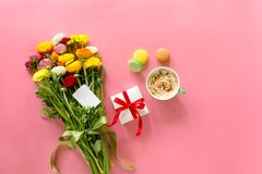 Festive morning concept buttercup flowers bouquet, gift box, cup of cappuccino and makarons cake on the pink background with copy stock photography