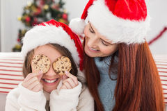 Festive mother and daughter on the couch with cookies Stock Images