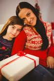 Festive mother and daughter holding christmas present Stock Photos