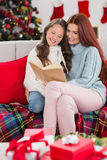 Festive mother and daughter reading on the couch Royalty Free Stock Photos