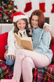 Festive mother and daughter reading on the couch Royalty Free Stock Photo