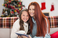 Festive mother and daughter using tablet on the couch Stock Photo
